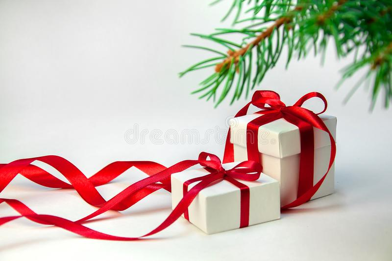Cadeau de Noël dans le boîtier blanc avec le ruban rouge sur le fond clair avec l'arbre de sapin Composition en vacances de nouve images stock