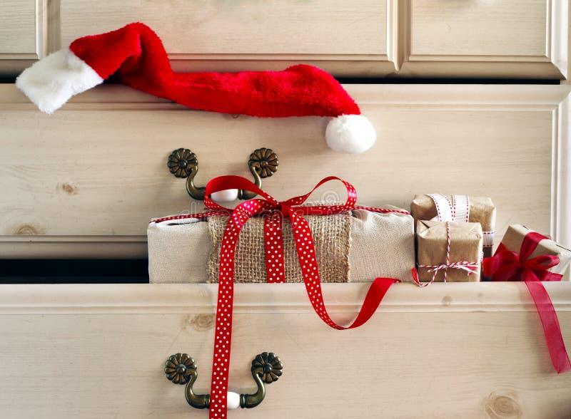 Cadeau de Noël et chapeau de Santa Claus dans le tiroir de raboteuse photographie stock