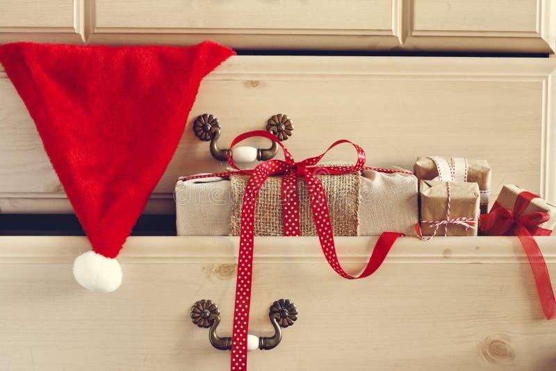 Cadeau de Noël et chapeau de Santa Claus dans le tiroir de raboteuse image libre de droits