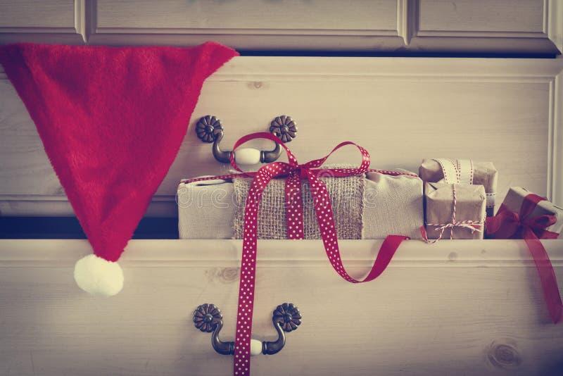 Cadeau de Noël et chapeau de Santa Claus dans le tiroir de raboteuse photo stock