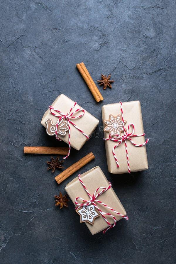 Cadeau de Noël ou boîte actuelle enveloppée en papier d'emballage avec la décoration sur le fond foncé Présent décoré des biscuit photographie stock libre de droits