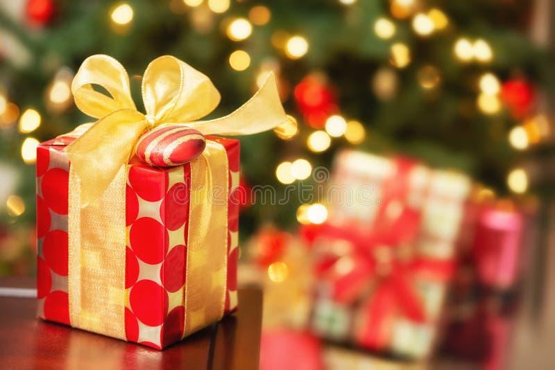 Cadeau de Noël rouge et d'or avec un arc et un ornement photos stock