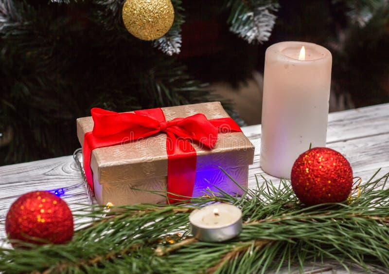 Cadeau du ` s de nouvelle année et une bougie brûlante avec des jouets de boules de Noël sur un fond en bois blanc, vacances du ` photo stock