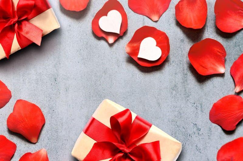 Cadeau en papier de métier avec la décoration de coeur sur les pétales de rose rouges Concept Romance Configuration plate, vue su photographie stock libre de droits