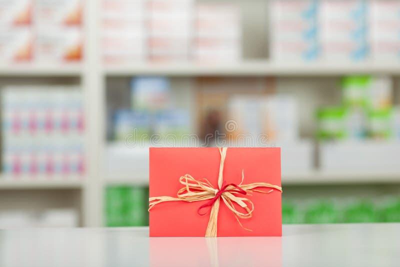 Cadeau enveloppé dans le papier et l'arc rouges au compteur de pharmacie photographie stock libre de droits