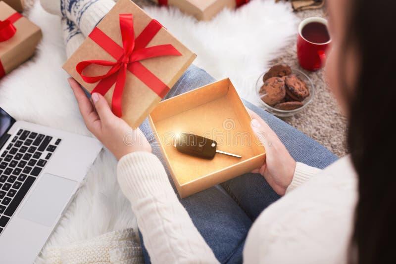 Cadeau et houx Cadeau de Noël d'ouverture de femme avec la clé de voiture image libre de droits