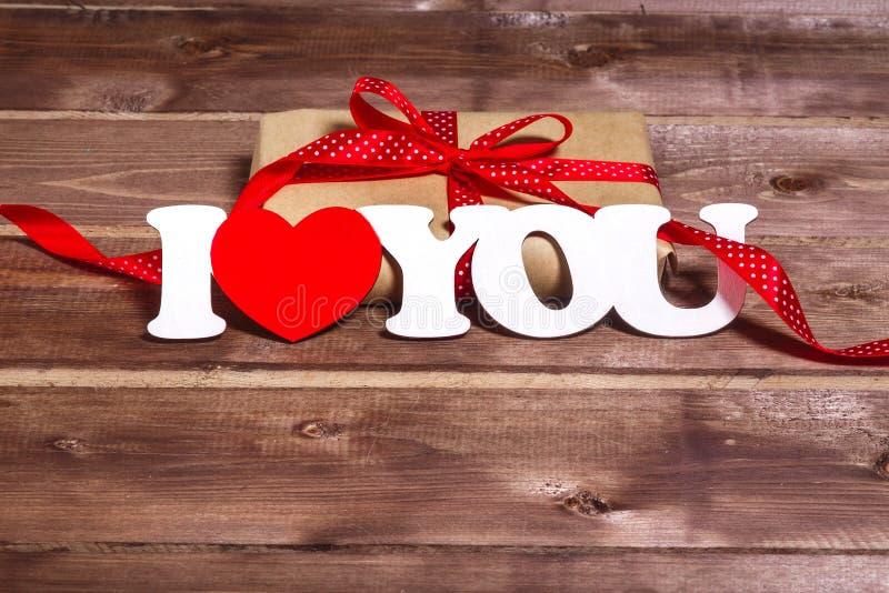 Cadeau et le ` de ` de mots je t'aime sur un fond en bois valentines de rouge de coeur de jour Carte de jour de Valentine images stock