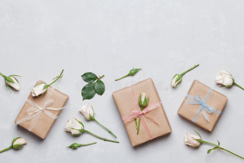Cadeau ou boîte actuelle enveloppée en papier d'emballage et fleur rose sur la vue supérieure grise de table Dénommer plat de con images stock