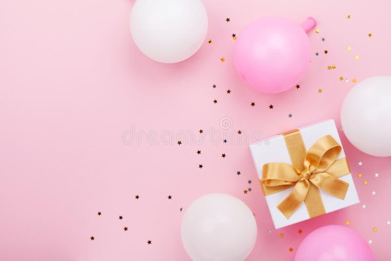 Cadeau ou boîte, ballons et confettis actuels sur la vue supérieure rose de table Composition plate en configuration pour l'anniv photographie stock libre de droits