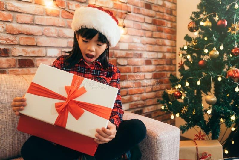 Cadeau ouvert de fille de Noël avec le ruban rouge à la maison photographie stock libre de droits