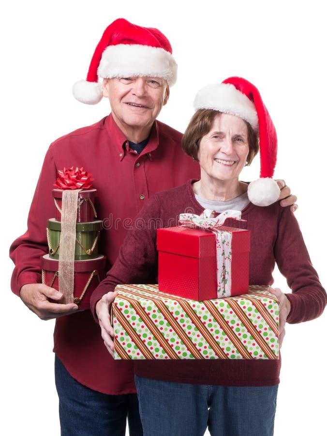 Cadeaux aînés heureux de Noël de roulement de couples image libre de droits