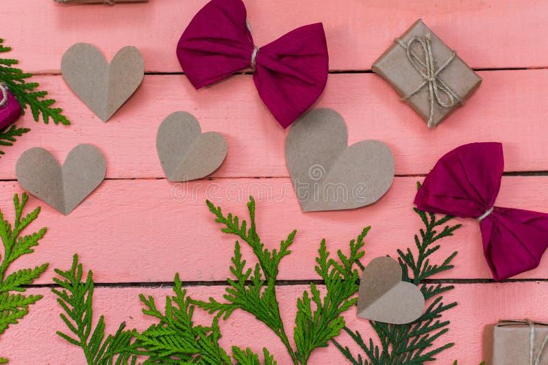 Cadeaux, arcs et coeurs sur le fond en bois rose photos libres de droits