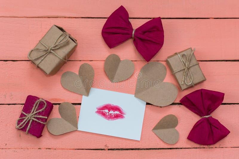 Cadeaux, coeurs et une carte avec une copie de lèvre sur un fond en bois rose photographie stock libre de droits