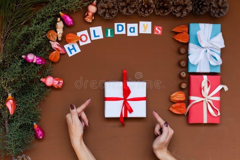 Cadeaux de décor de vacances d'hiver de décoration d'arbre de nouvelle année de fond de Noël des mains des femmes photos stock