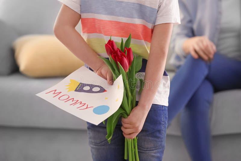Cadeaux de dissimulation de petit garçon pour la mère derrière le sien de retour à la maison photo libre de droits