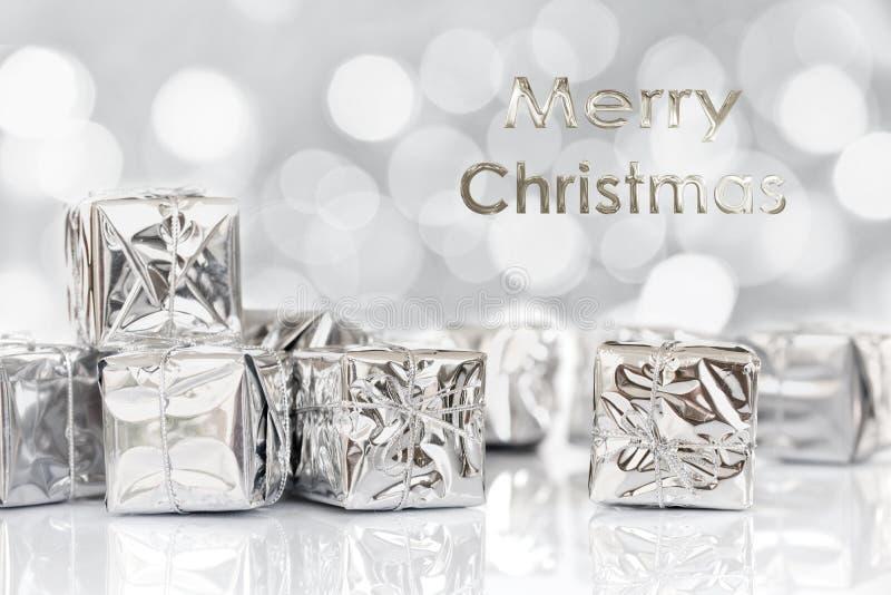 Cadeaux de Joyeux Noël en papier argenté brillant, fond de bokeh images stock