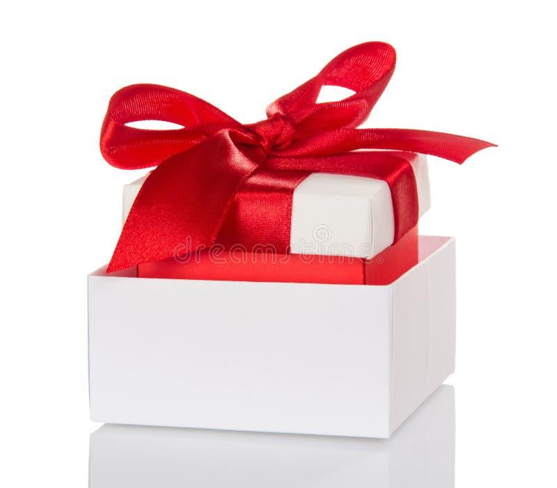 Cadeaux de Noël, décorés de l'arc rouge dans le boîtier blanc d'isolement dessus image libre de droits