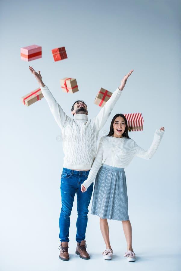 cadeaux de Noël enveloppés en baisse contagieux de couples multiculturels photos libres de droits