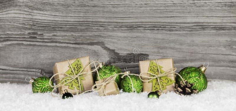 Cadeaux de Noël et boules vertes sur le vieux fond gris en bois photo stock