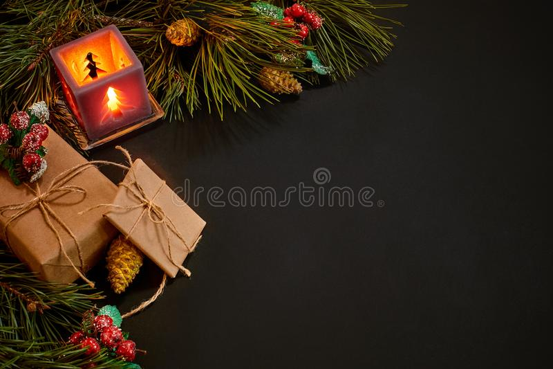 Cadeaux de Noël et chandelier rouge près de branche impeccable verte sur un fond noir Fond de Noël Vue supérieure image stock