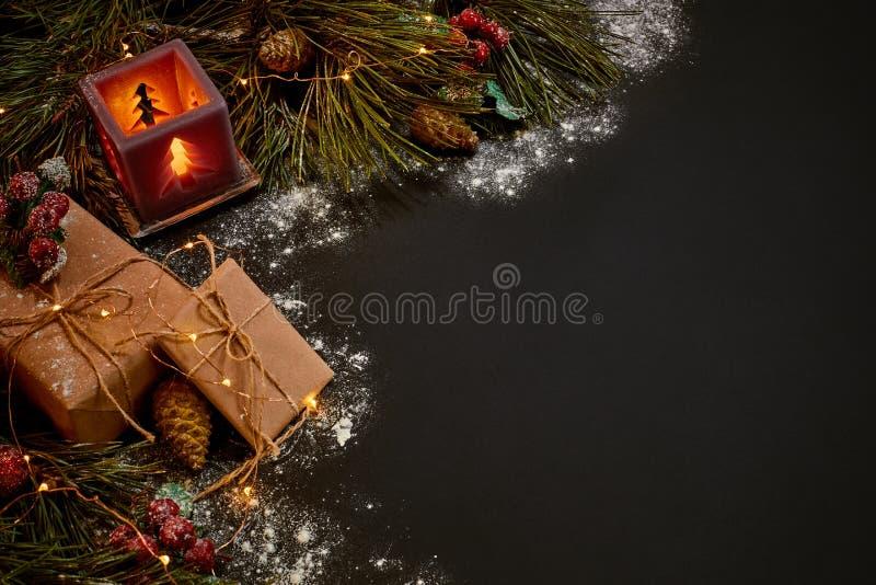 Cadeaux de Noël et chandelier rouge près de branche impeccable verte sur un fond noir Fond de Noël Vue supérieure photos libres de droits