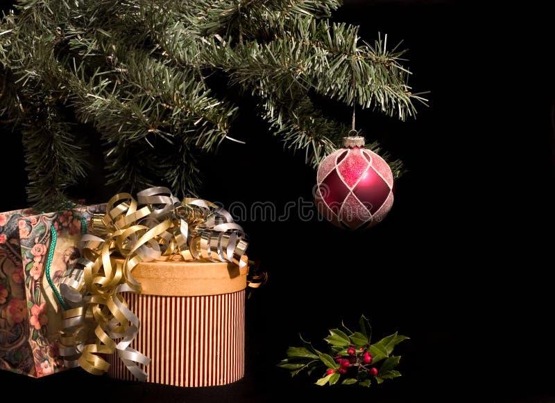 Cadeaux de Noël sous l'arbre avec le houx image libre de droits