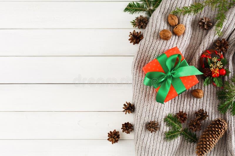 Cadeaux de Noël sur le fond en bois blanc de table Écharpe, boîte de Noël, branche de sapin photos stock