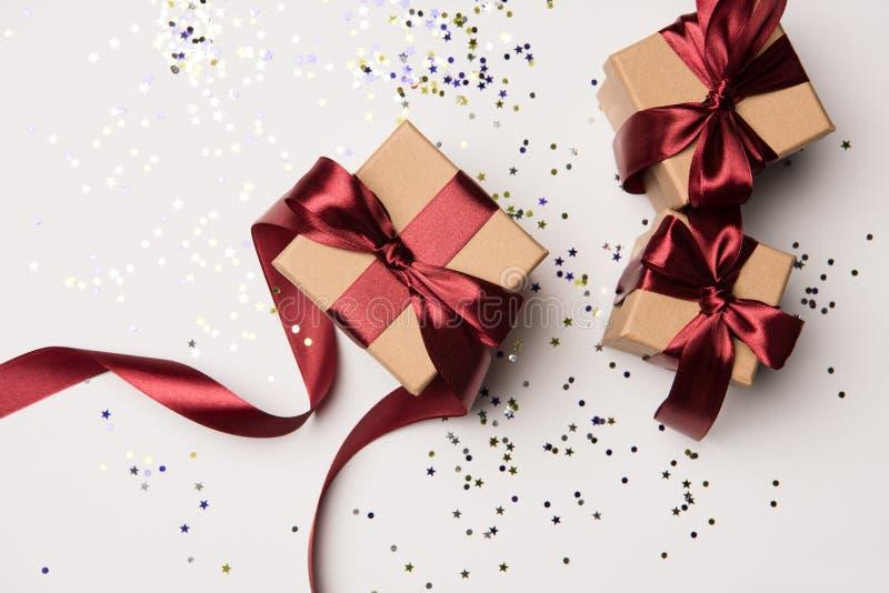 Cadeaux disposés avec les rubans rouges et confettis d'isolement sur le blanc image stock