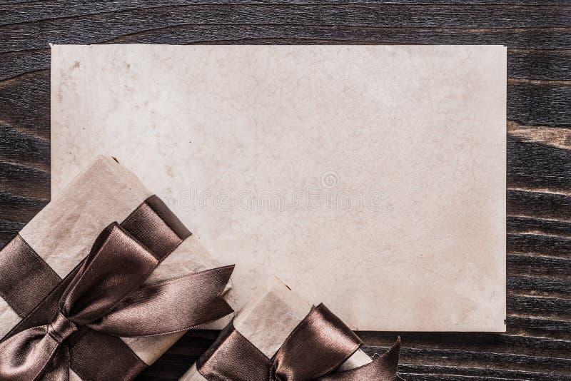 Cadeaux enfermés dans une boîte avec le papier attaché de rubans sur le conseil en bois photographie stock