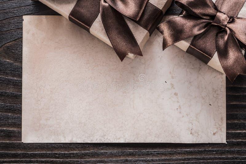 Cadeaux enfermés dans une boîte avec le papier brun attaché de rubans sur le conseil en bois photo stock