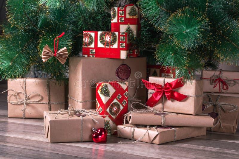 Cadeaux enveloppés se trouvant sous l'arbre de Noël photo stock