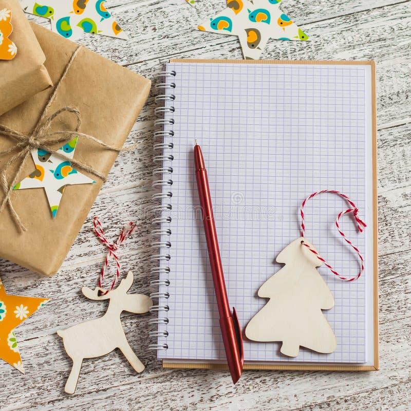 Cadeaux ouverts de bloc-notes, de Noël de blanc et décorations de Noël sur une surface en bois légère image stock