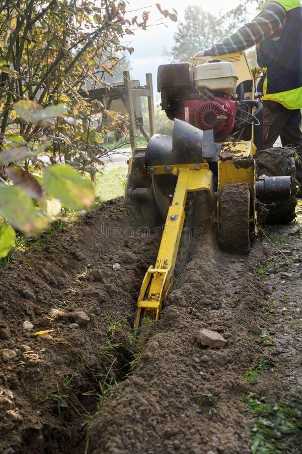 Cadeeiro de corrente motora em ação, equipamento de construção de máquinas de escavação para colocar cabos em trincheiras estreit fotos de stock
