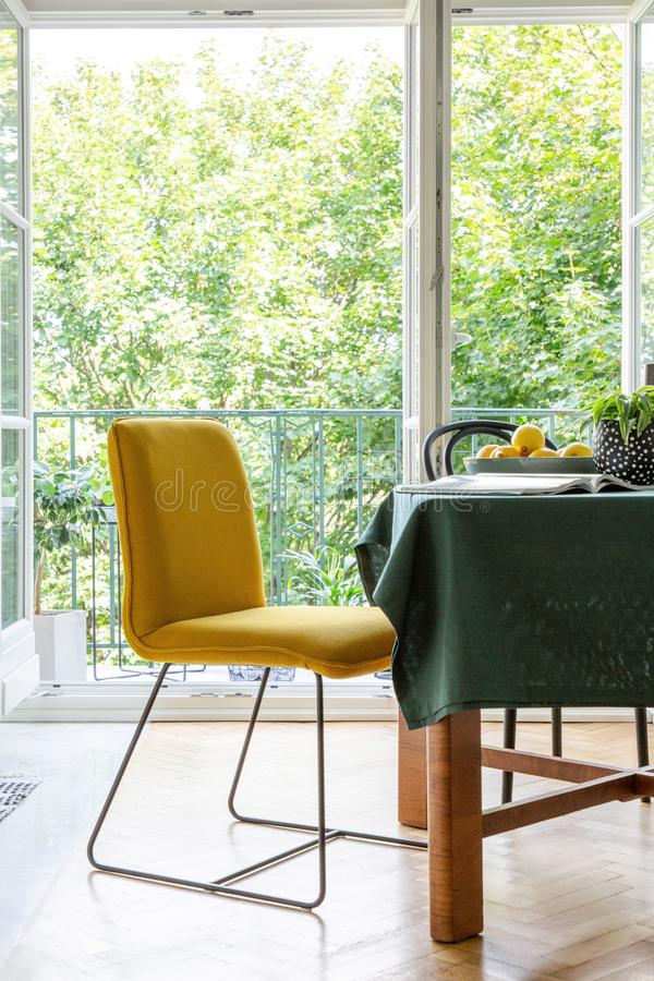 Cadeira amarela ao lado de uma tabela em um interior da sala de jantar com um terraço foto de stock royalty free