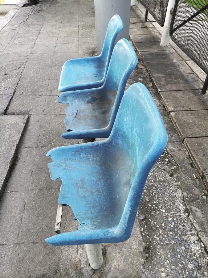 Cadeira azul quebrada na parada do ônibus imagem de stock