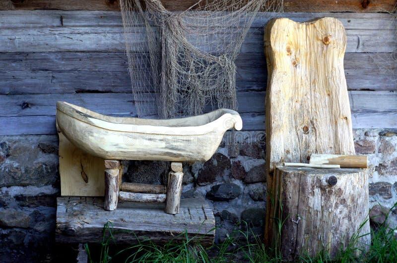 Cadeira, berço e rede de pesca feitos a mão de madeira no fundo da parede da casa de log Foto imóvel retro da vida do vintage Ext foto de stock royalty free