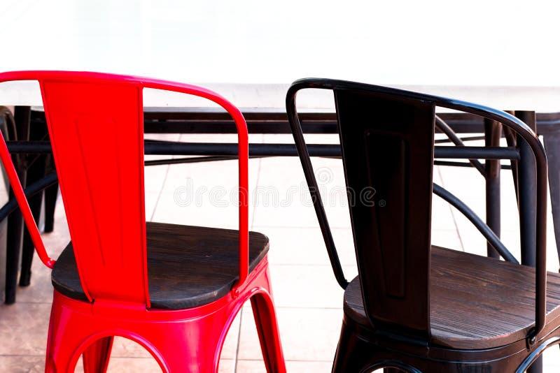 Cadeira branca da tabela, a vermelha e a preta no restaurante Ascendente fechado fotografia de stock royalty free