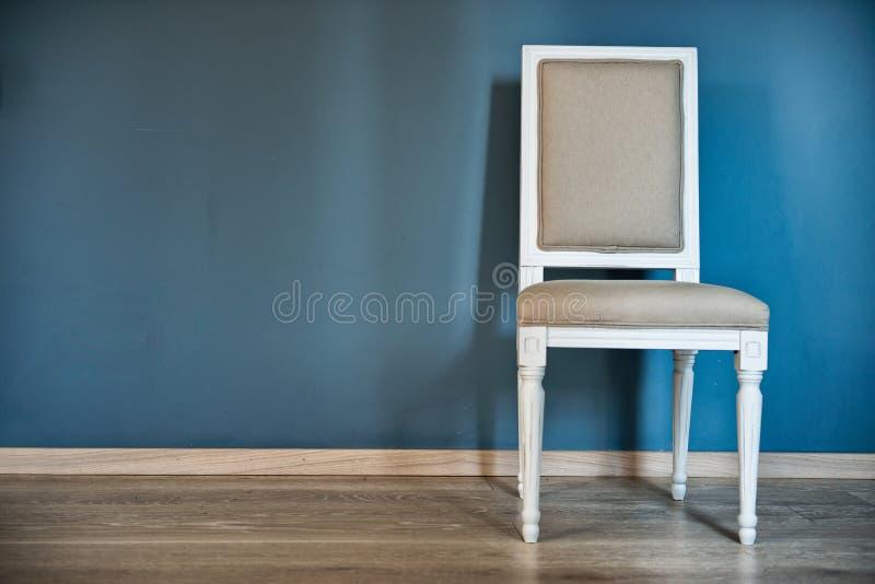 Cadeira branca perto da parede azul imagens de stock