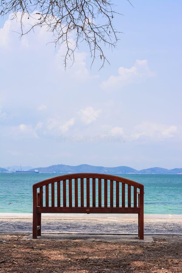 A cadeira com a árvore pelo oceano foto de stock royalty free