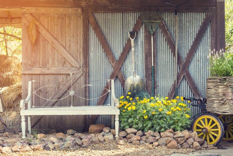 Cadeira com as ferramentas de jardim na exploração agrícola do vintage da luz do sol, vintage fi imagem de stock royalty free