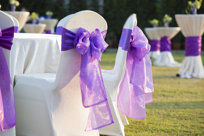 Cadeira com uma curva roxa em um casamento bonito imagem de stock