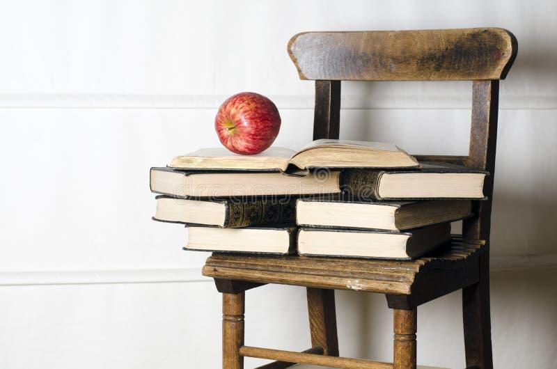 Cadeira da escola do vintage da criança com livros velhos foto de stock royalty free