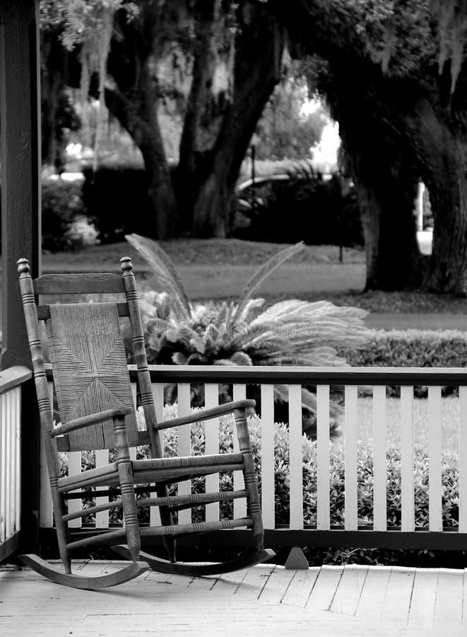 Cadeira de balanço de Adirondack com assento do bastão no pátio de entrada coberto velho da casa fotos de stock royalty free