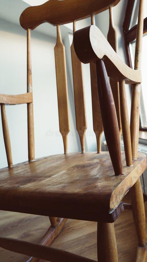 Cadeira de balanço de madeira do vintage no assoalho velho abandonado do sótão Janela e balcão à rua fotografia de stock