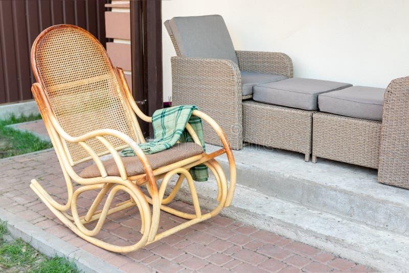 Cadeira de balanço de madeira vazia do rattan com a manta verde da flanela no quintal do terraço da casa fora Exterior calmo da c imagem de stock royalty free
