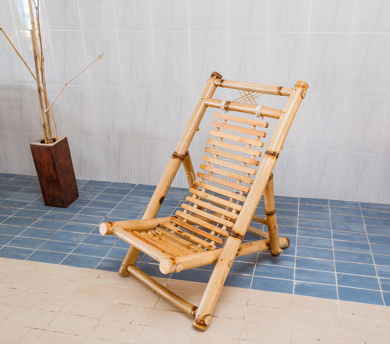 Cadeira de bambu natural à moda bonita surpreendente que está no assoalho cerâmico azul e bege imagem de stock