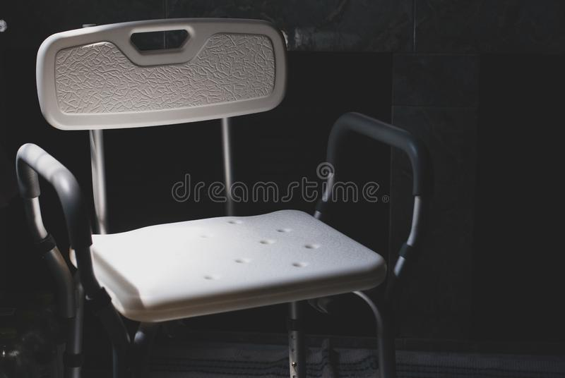 A cadeira de banho plástica para a pessoa idosa ou os deficientes motores da rega posta na luz deixando escura vêm do lado esquer imagem de stock
