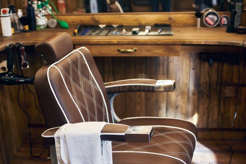 Cadeira de barbeiro vazia no interior de madeira Local de trabalho do vintage no estúdio para cortes de cabelo Tema do fundo do b imagens de stock royalty free