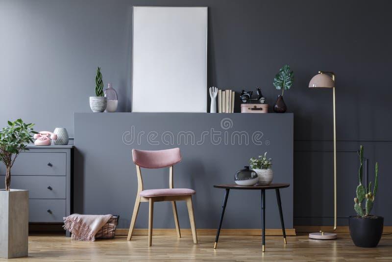 Cadeira de madeira cor-de-rosa na tabela preta no interior cinzento da sala de visitas com o modelo do cartaz vazio fotos de stock royalty free