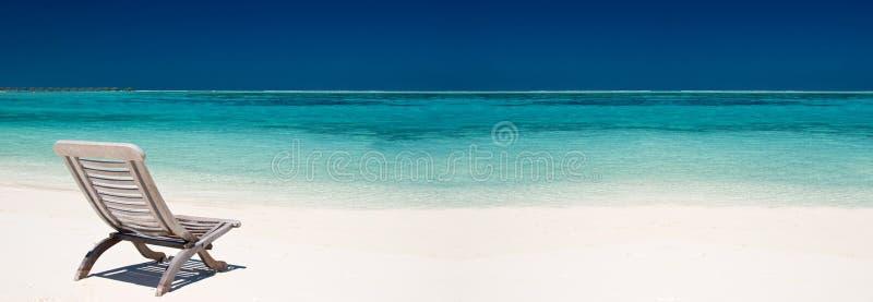 Cadeira de madeira da lona em uma praia tropical bonita imagens de stock royalty free